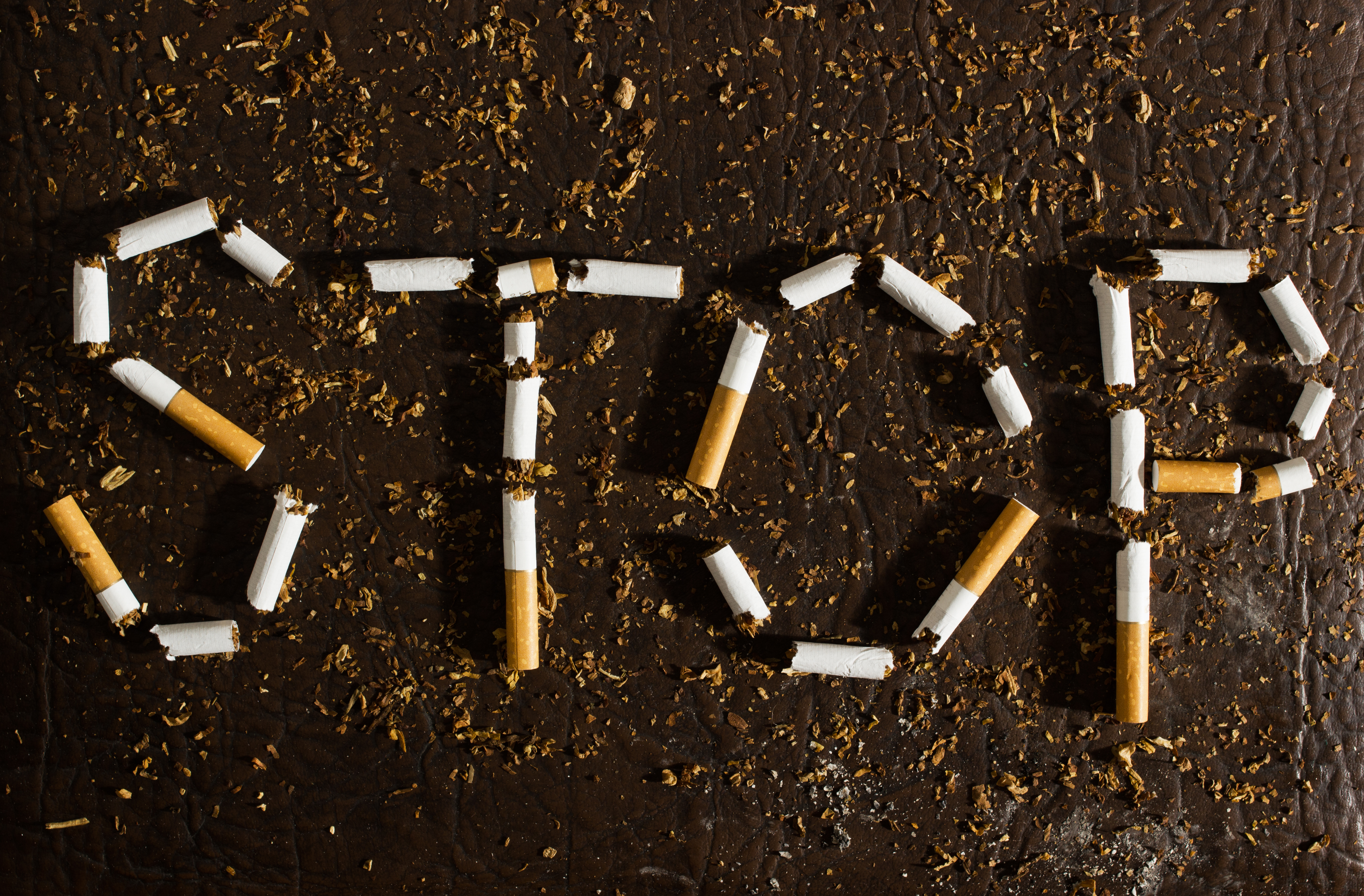 the word STOP spelled out in broken tobacco cigarettes