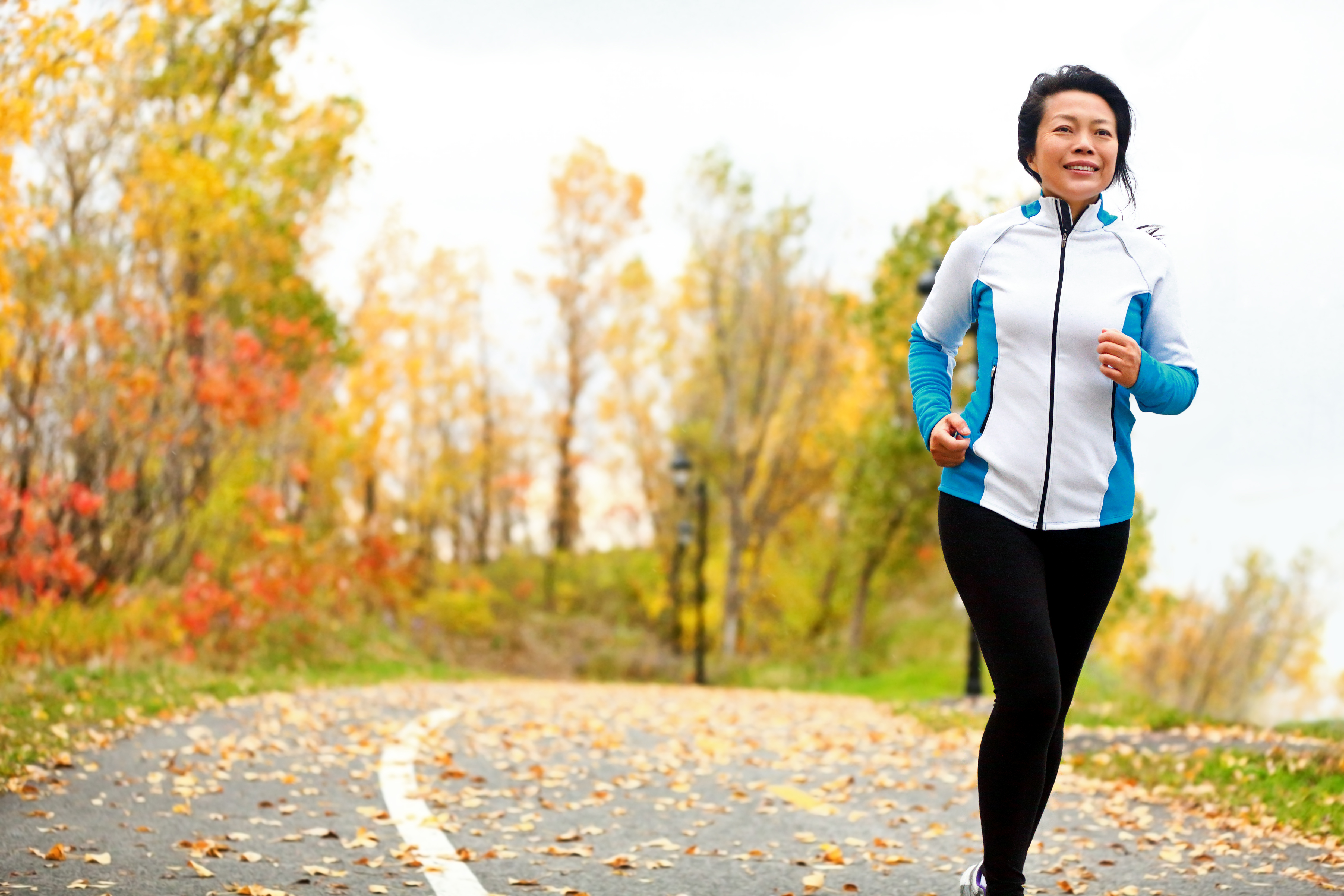 a healthy Asian woman exercising and running on street covered in fallen autumn leaves