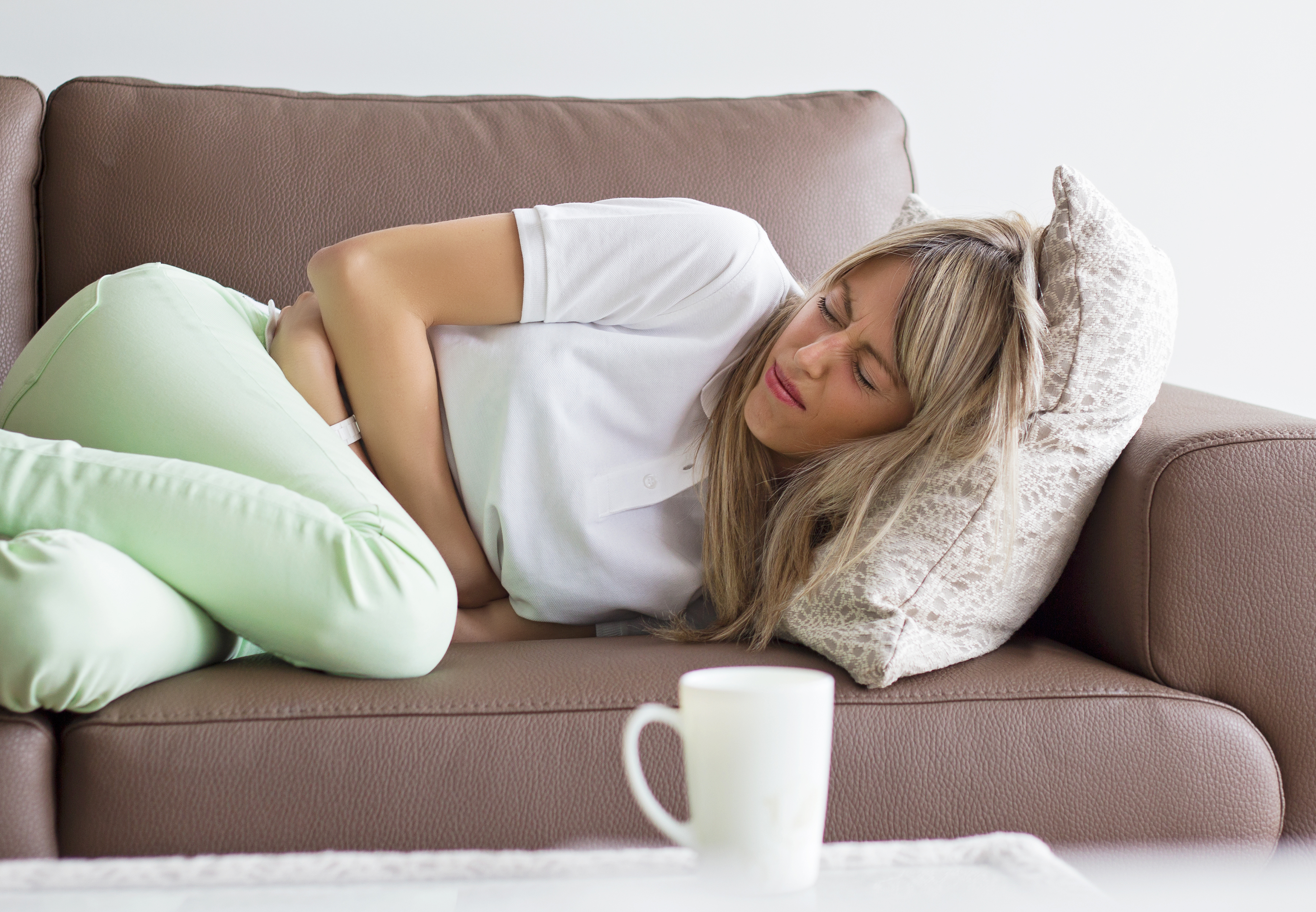 woman on couch having menstrual cramps or intestinal stomach pain