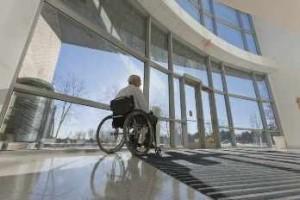 Hombre en silla de ruedas frente a la entrada adaptada del hospital
