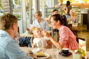 family eating in restaurant with mother feeding baby