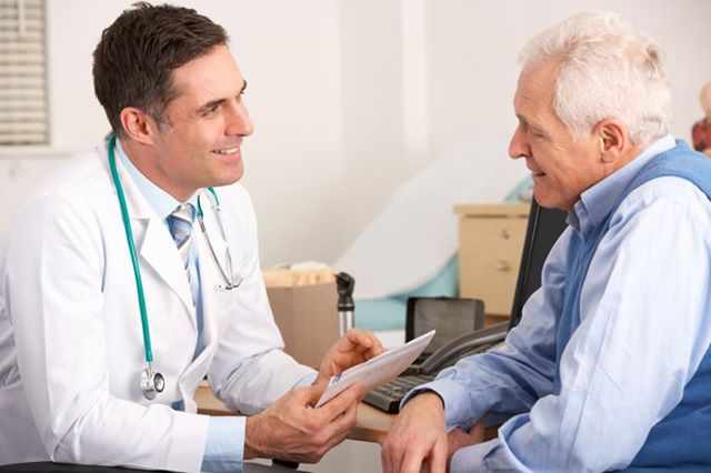 a male doctor talking with an elderly male patient