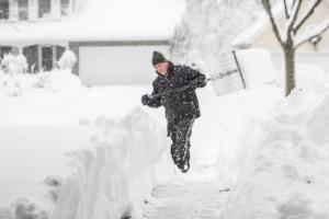 man shoveling deep snow in winter