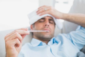 Sick man with cold or flu lying on sofa checking his temperature for a fever