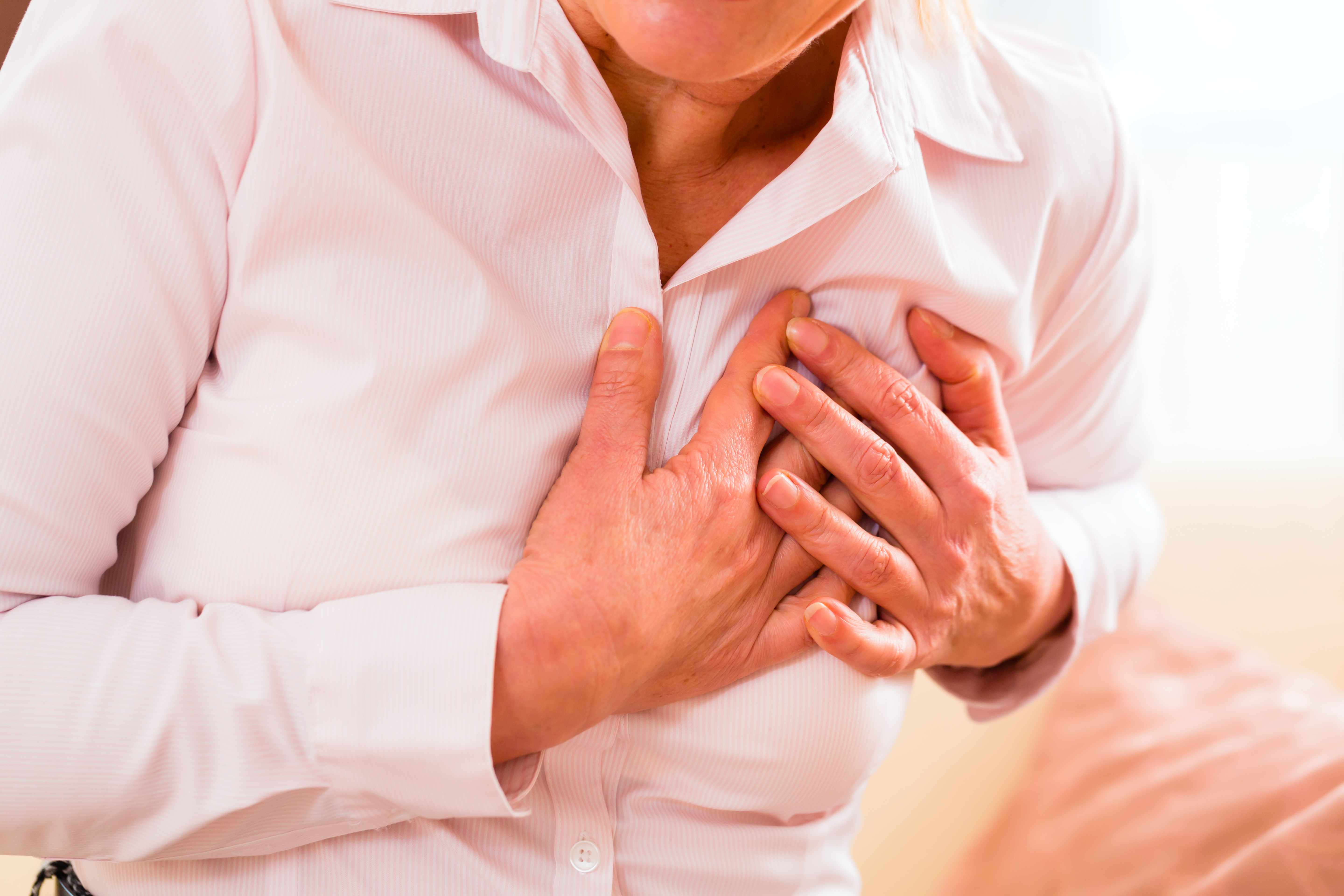 older woman holding chest because of heart infarction