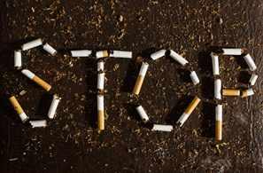 La palabra STOP (dejar de fumar) aparece sobre unos cigarrillos