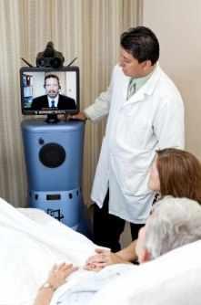 Un médico y un paciente miran a la máquina para atención a distancia del accidente cerebrovascular