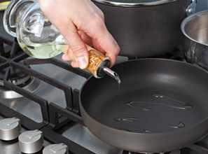 Aceite para cocinar vertido desde una botella de cristal a la sartén