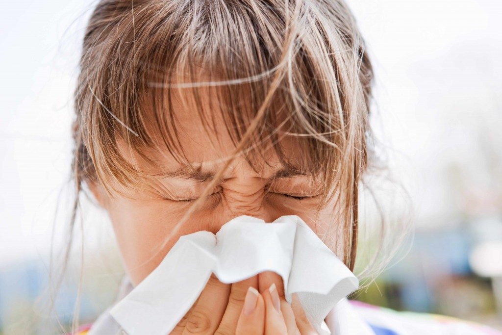 young girl blowing her nose in a kleenex