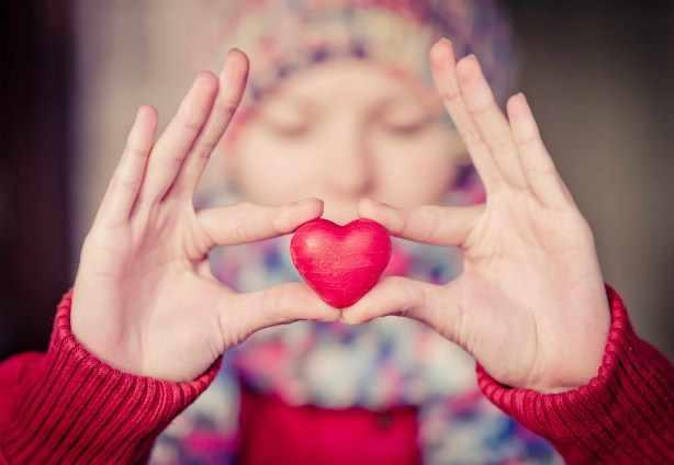 una mujer sostiene una piedra con forma de corazón rojo