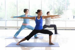 Two women, one man, doing a yoga pose with their arms stretched out from their sides and leaning on their left leg in a squatted position