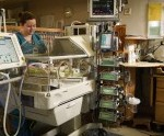 Nurse caring for a neonate in an incubator