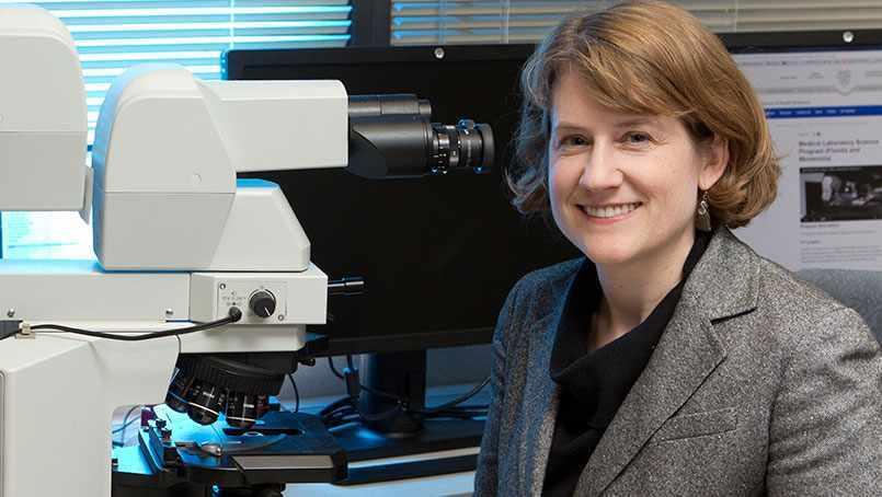 researcher Dr. Bobbi Pritt with lab microscope