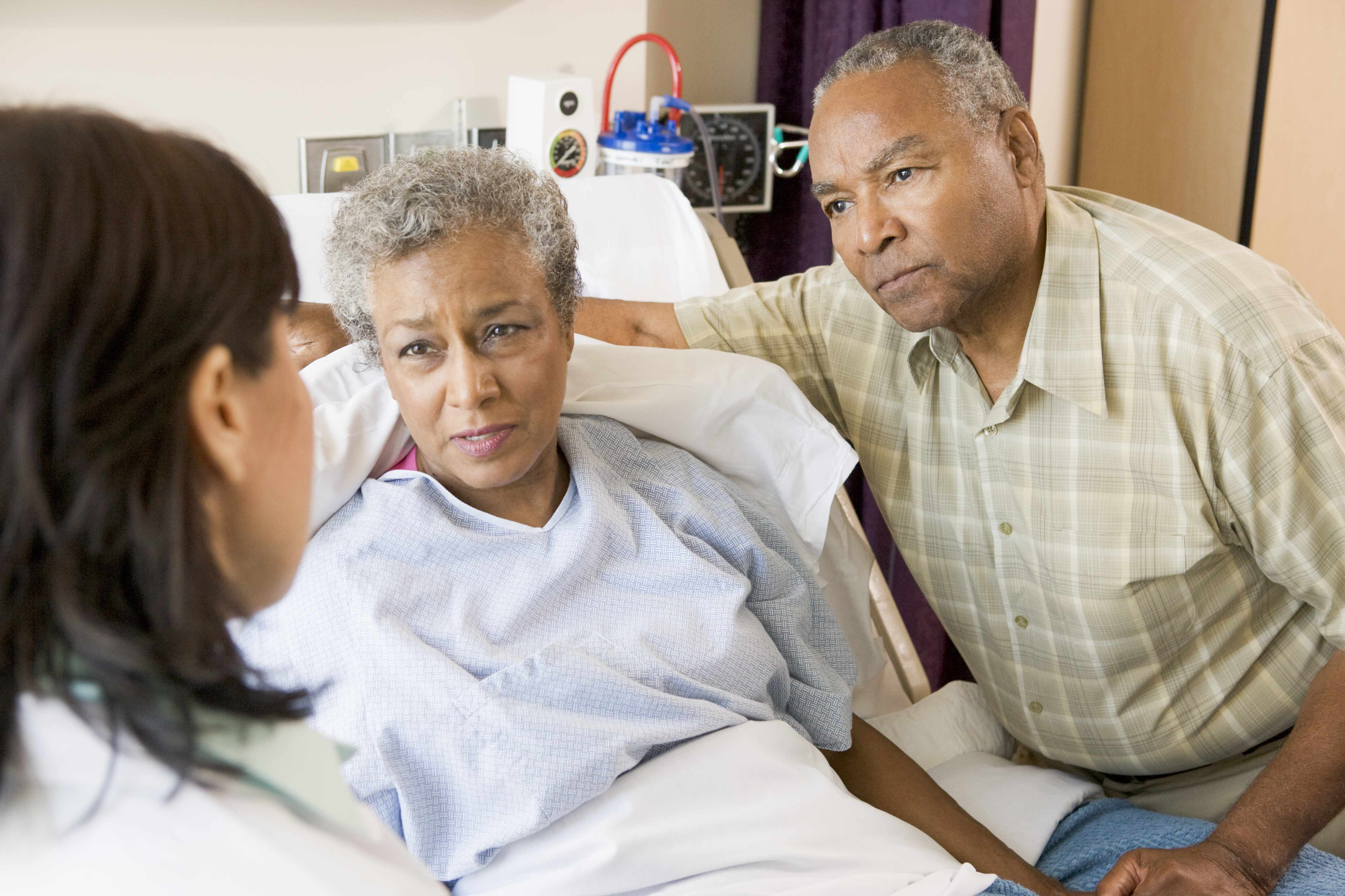 African-American woman in hospital bed listening to doctor