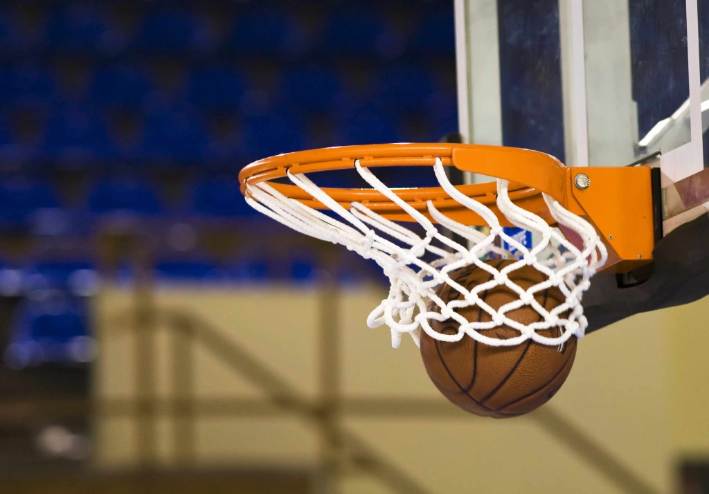 close up of basketball going through hoop - sports