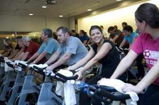 Hombres y mujeres pedalean en una clase de acondicionamiento físico