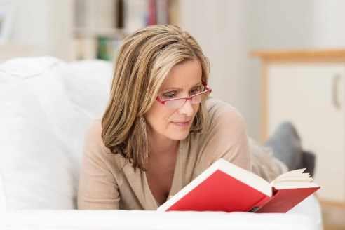 Mujer lee un libro con lentes de lectura