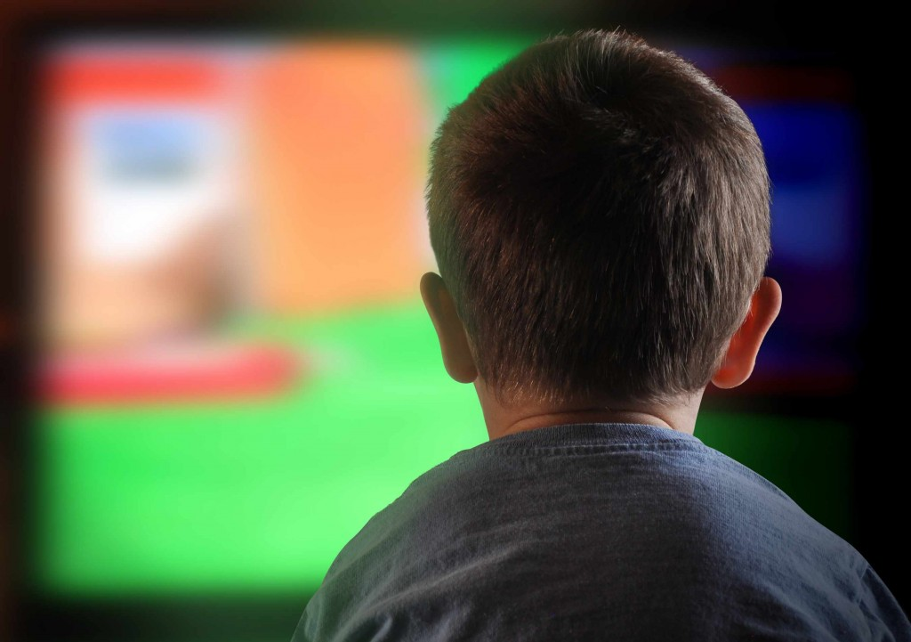 little boy staring at electric , digital television screen