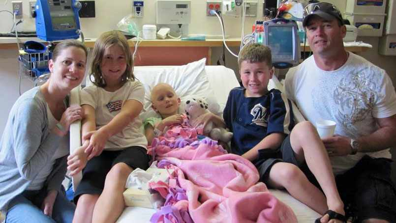Anika Chesak in hospital bed with her family nearby, proton beam therapy