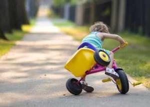 Una niña pequeña se cae de la bicicleta