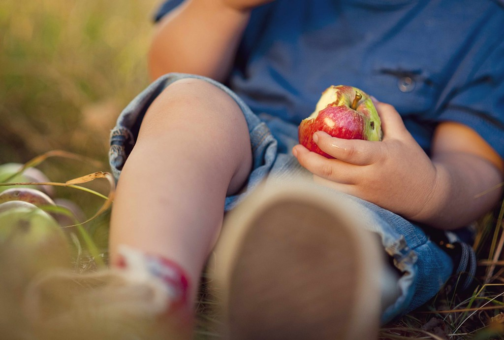 young child sitting on the ground and eating an apple, healthy eating