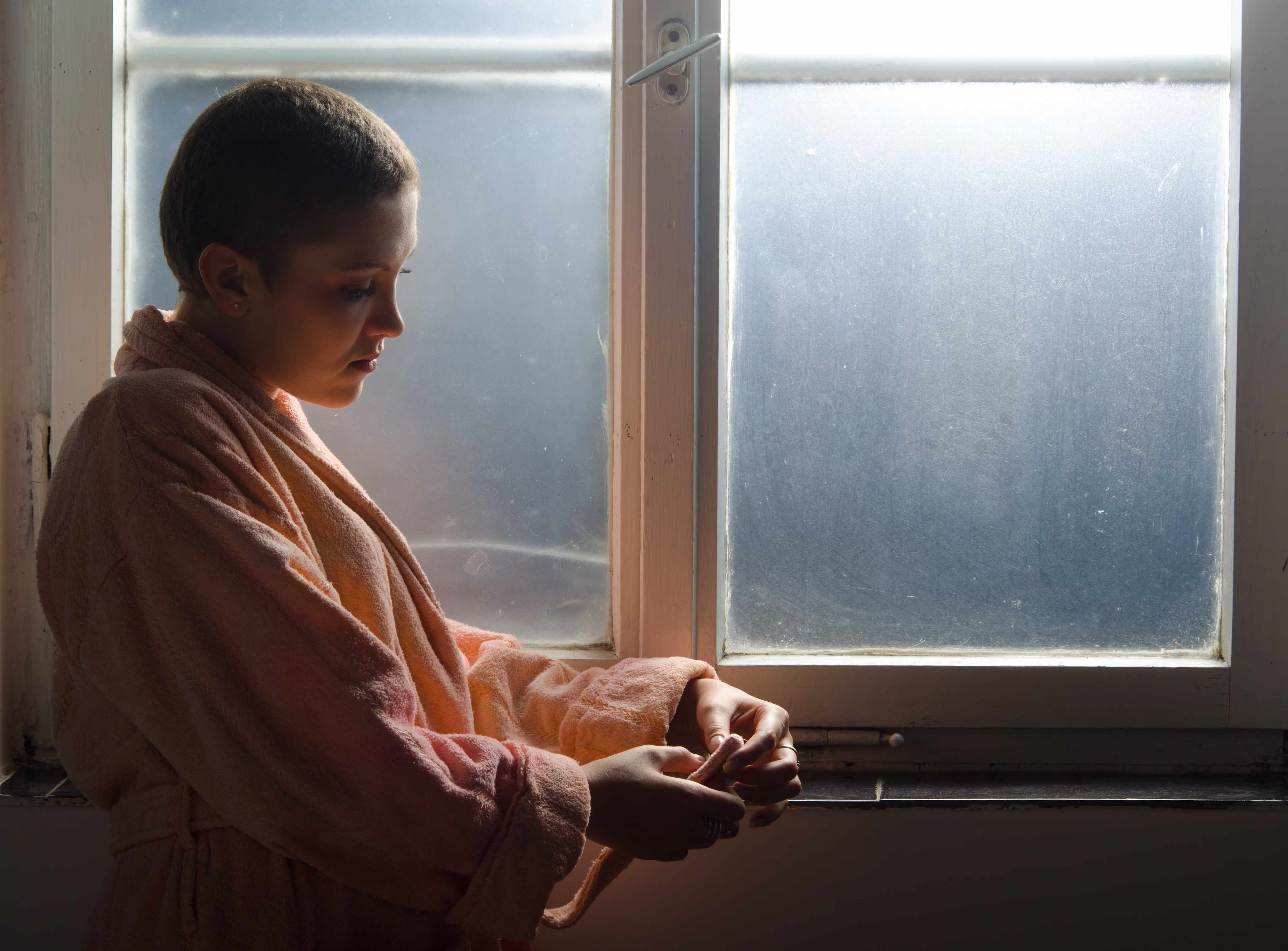 young cancer patient standing by window thinking