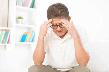 Cuadro de un hombre maduro con dolor de cabeza, sentado en el sofá de su casa