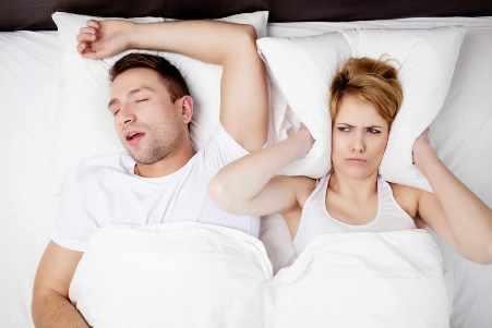 Una mujer se tapa los oídos para no escuchar al hombre roncar