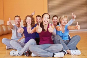 gym class of people exercising, showing the 'thumbs up' sign