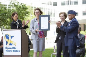 Stephanie Starr, M.D., receives the Yellow Ribbon plaque from (left to right) Annette Kuyper, Director of Military Outreach, Beyond the Yellow Ribbon; Tina Smith, Minnesota Lieutenant Governor; and Minnesota National Guard Air Force Brigadier General David Hamlar, M.D., D.D.S.