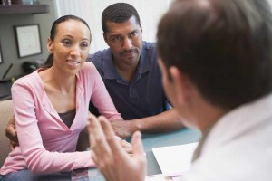 young African American couple conversing with physician, fertility