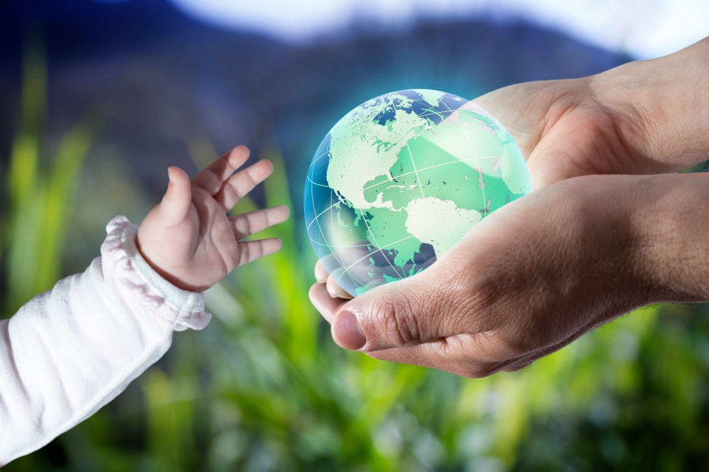 person holding a globe, the world, the earth and handing to a child