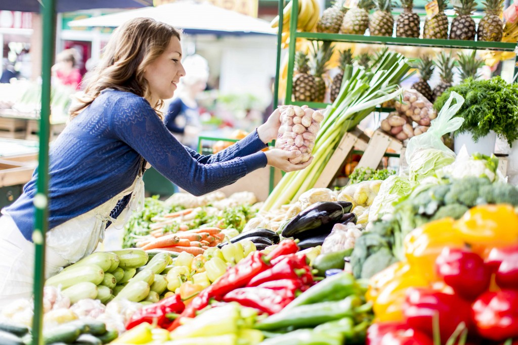woman at a farmers market or food stand picking out vegetables