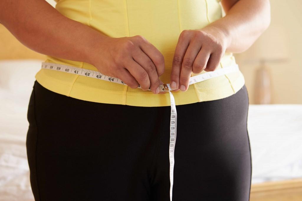 slightly overweight woman measuring waistline, stomach