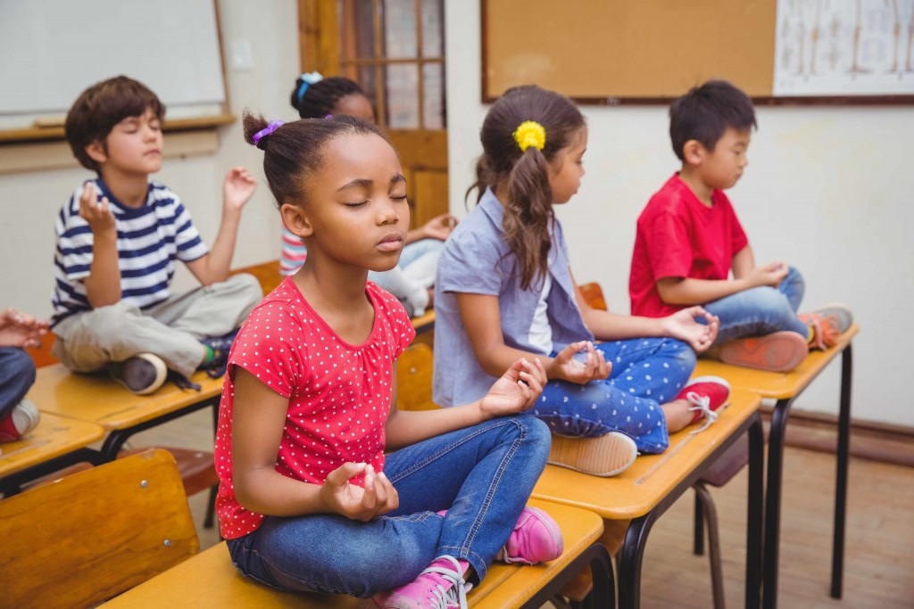 students relaxing and meditating in school classroom