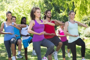fitness exercise group doing tai chi outside in park