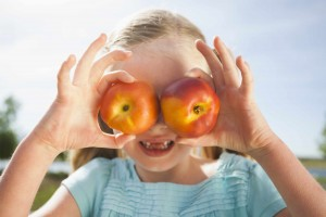 young girl, girl holding two apples over her eyes