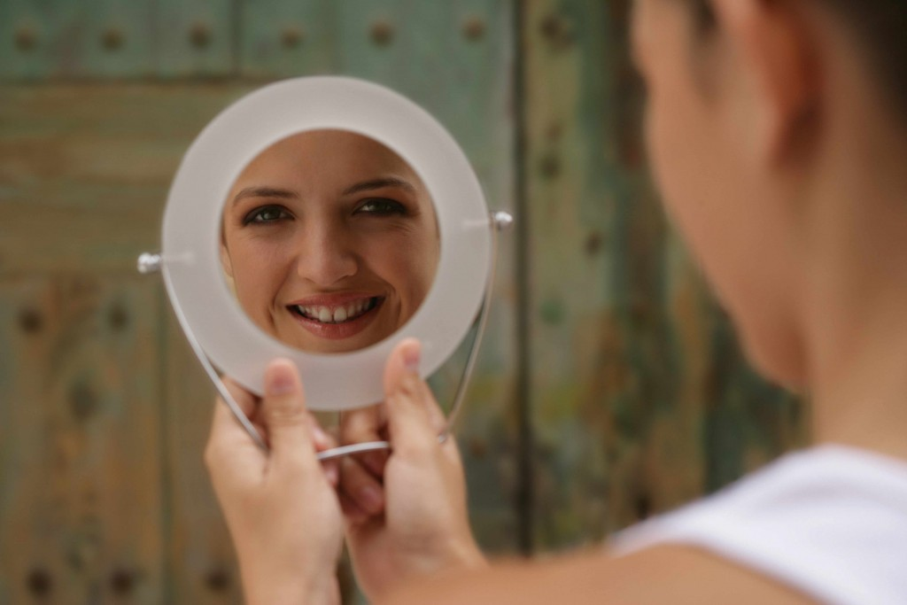 happy woman smiling at herself in a mirror