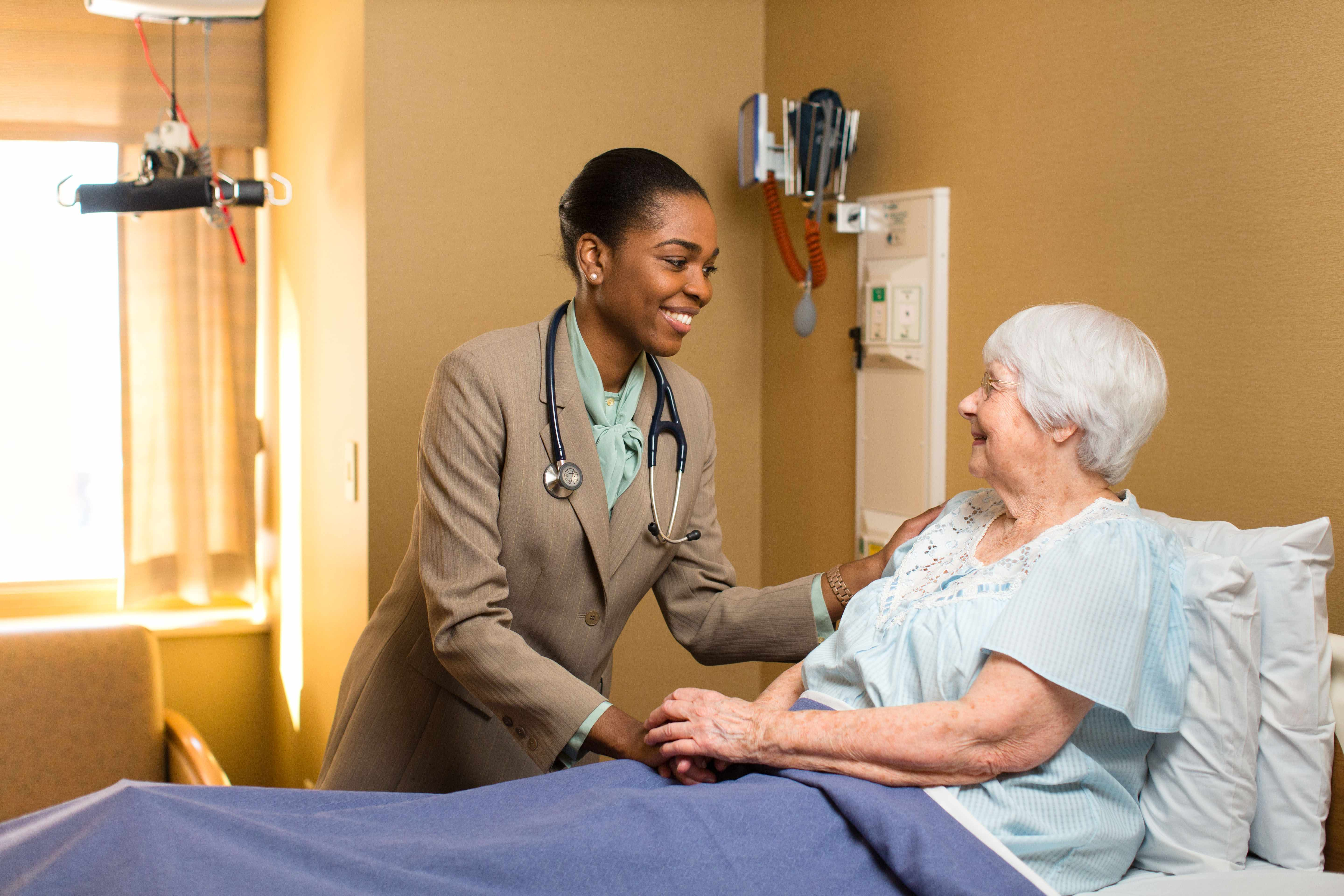 physician speaking with, examining elderly patient in hospital bed