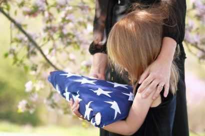 Un niña, acompañada por su madre, sostiene una bandera ante una tumba