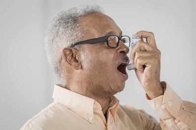 Un hombre usa un inhalador para el asma