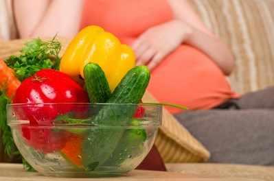 Una mujer embarazada come verduras sanas