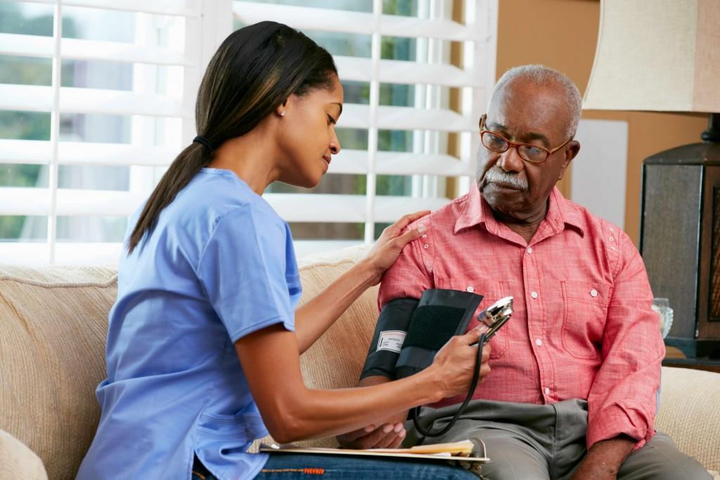 nurse visiting senior male patient at home, taking blood pressure