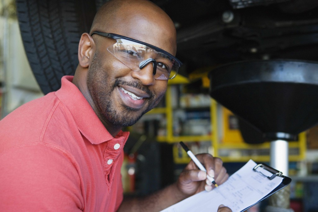 African-American man with working in garage wearing eye protection goggles