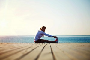 woman stretching in exercise gear, ocean boardwalk