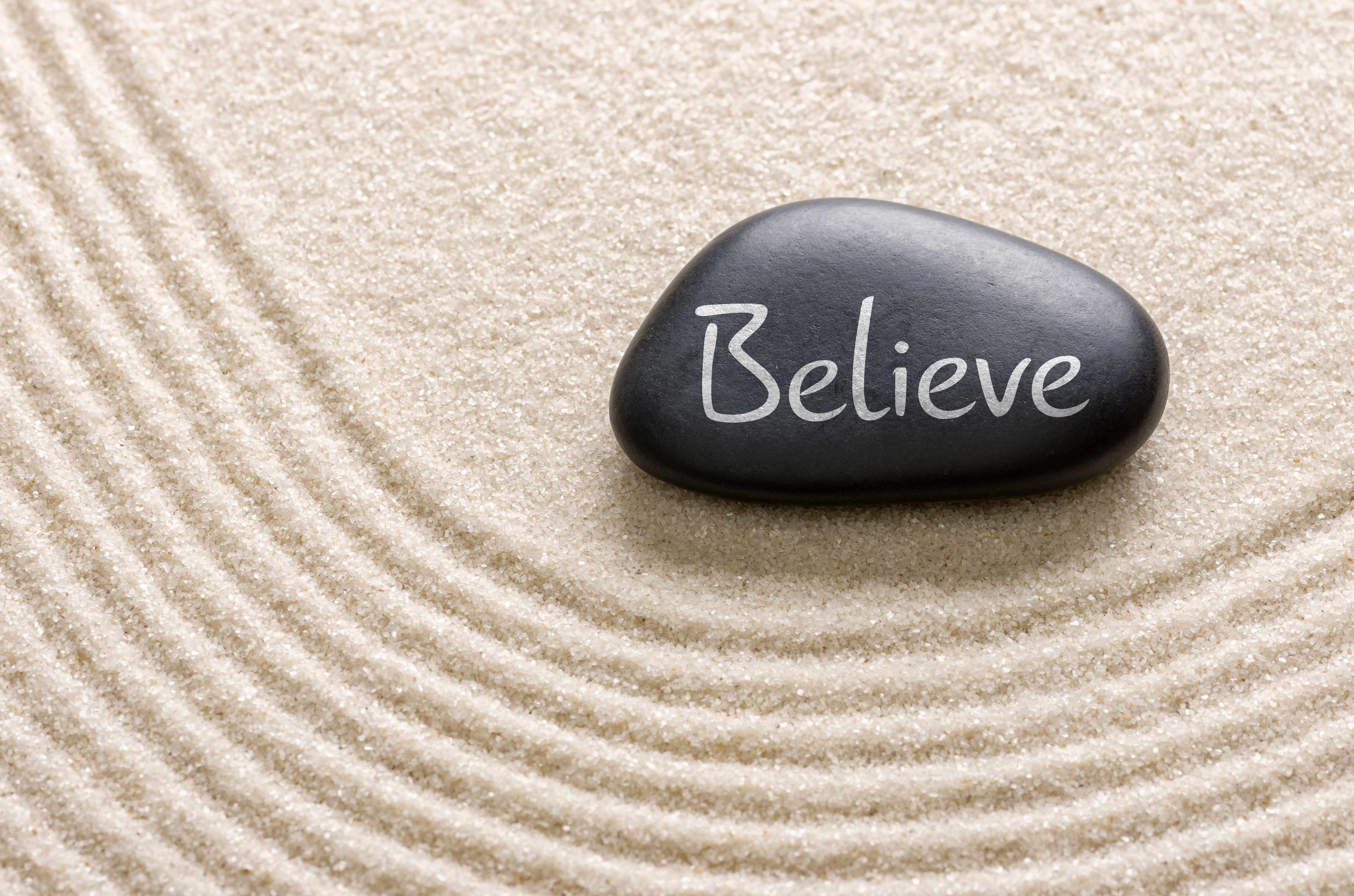 sand and stone with the word 'believe'