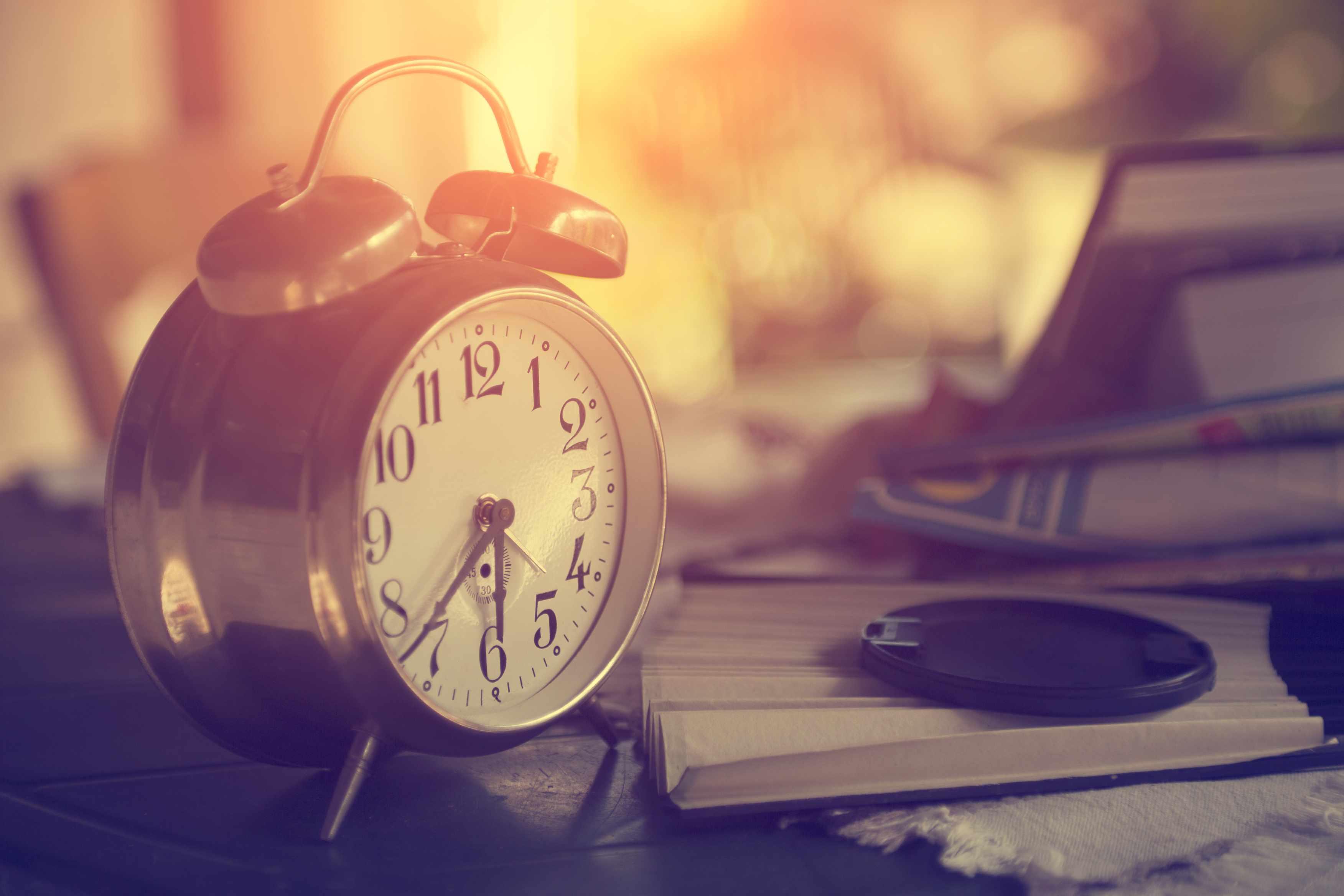 retro alarm clock on table with books