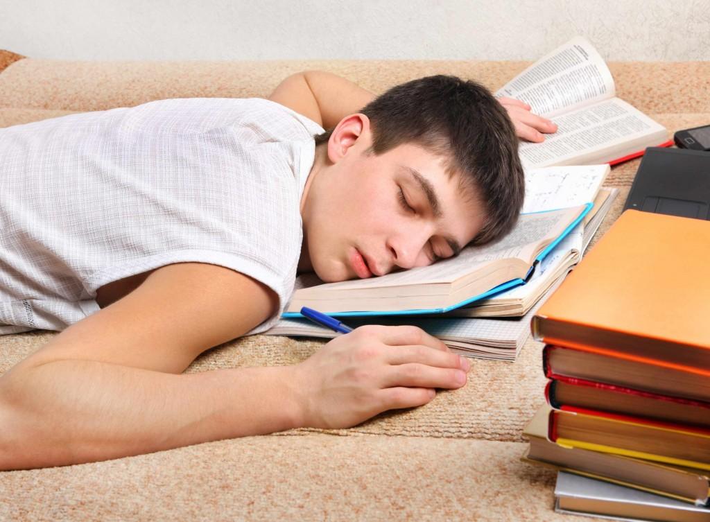 young teenage boy asleep on his school books