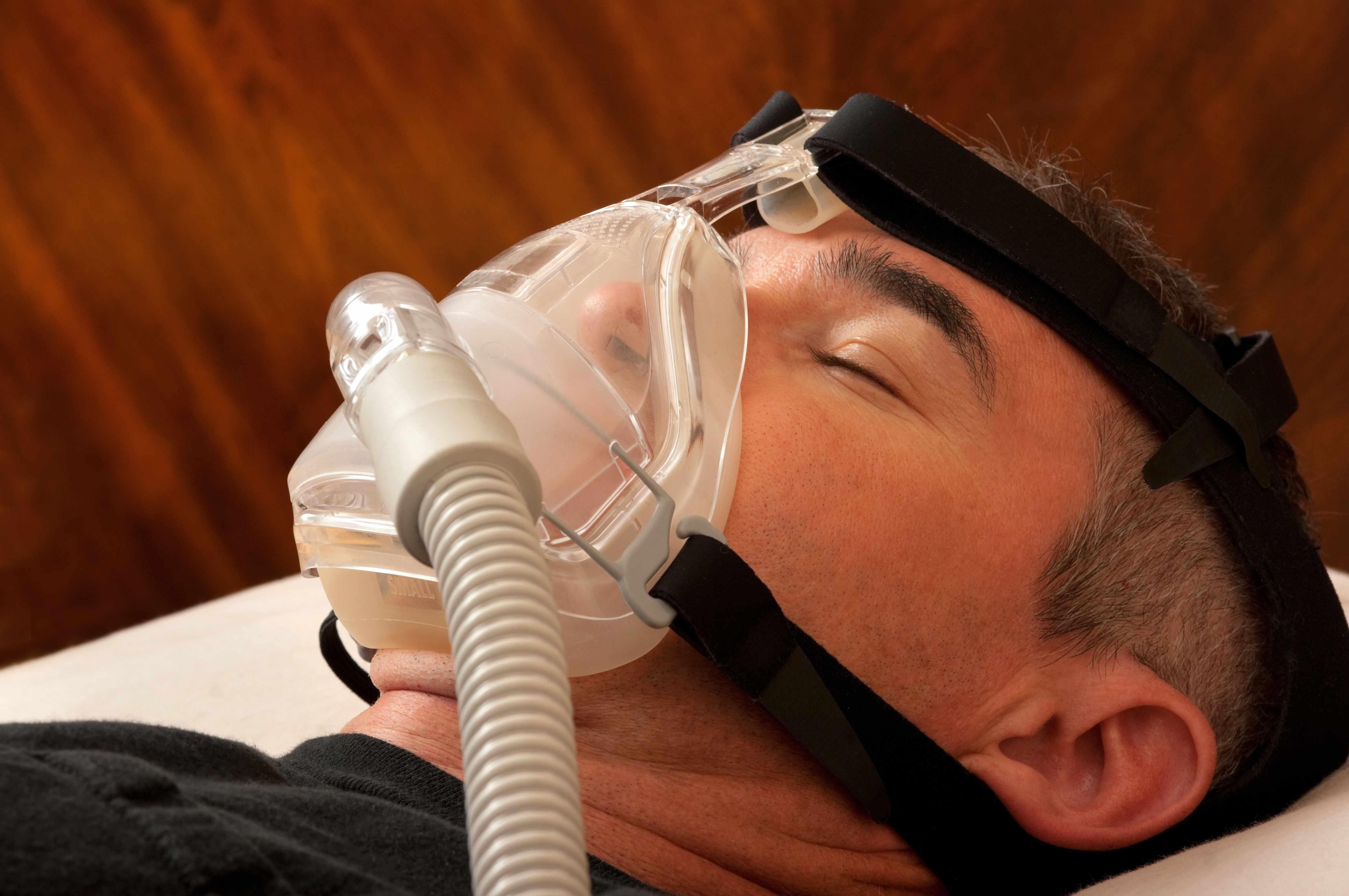 man sleeping with sleep apnea mask