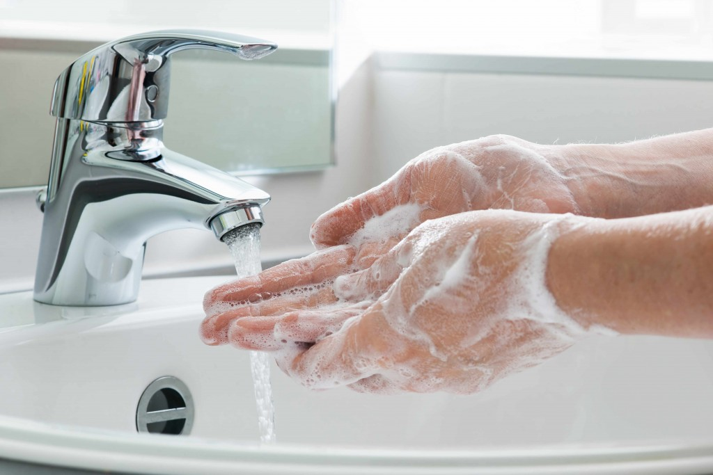 person washing hands in soap and water